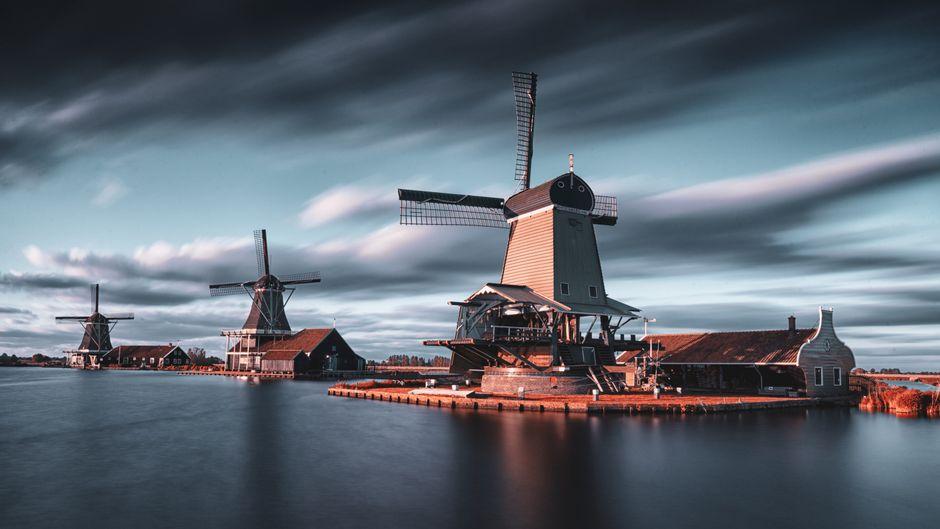 Windmühlen an einem Gewässer in den Niederlanden.
