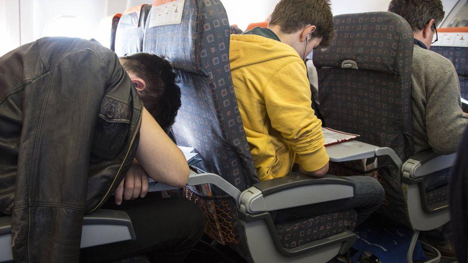 Ein Mann schläft an Bord eines Passagierflugzeuges über Berlin, Deutschland.