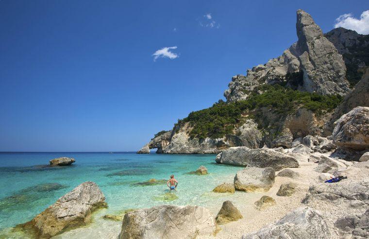 """Eine Frau steht am Strand  """"Cala Goloritzè"""" in Sardinien im Meer und schaut Richtung Felsentor."""