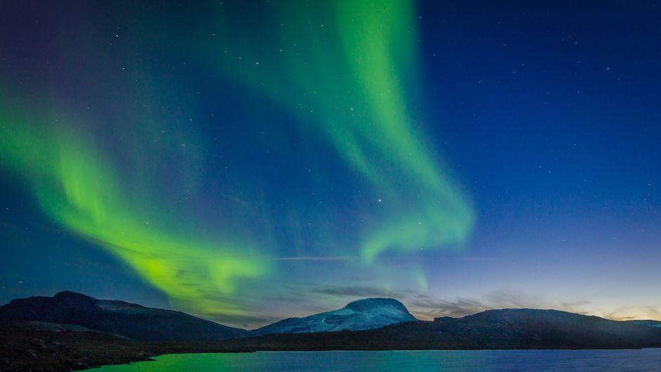 Polarlichter über einem See im Nationalpark Abisko in Schweden.