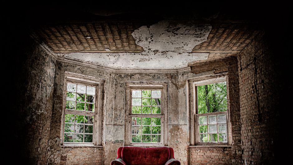 Ein rotes Sofa steht in einem verlassenen Gebäude.