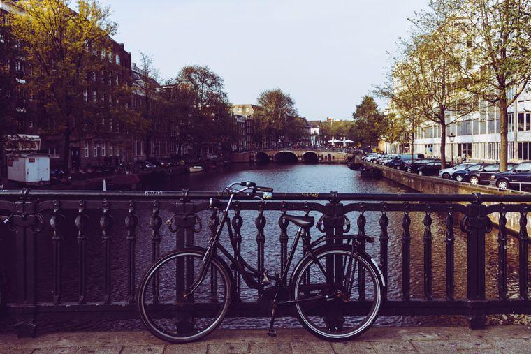 Ein Fahrrad vor einer Gracht in Amsterdam.