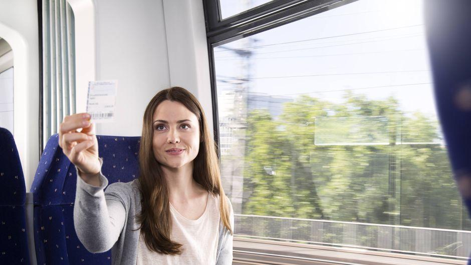 Eine Frau zeigt im Zug ihr Ticket.