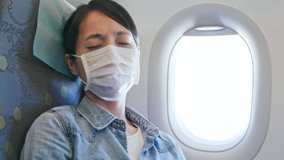 Eine Passagierin trägt einen Mundschutz.