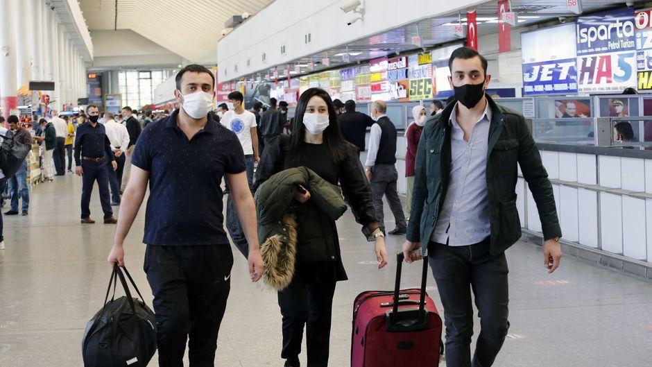 Reisende mit Gesichtsmasken an einem Busbahnhof in Ankara, Türkei.