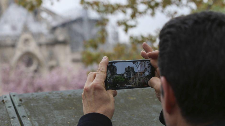 Passanten fotografieren die verkohlten Grundmauern der Kathedrale Notre-Dame in Paris, die bei einem Brand stark beschädigt wurde.