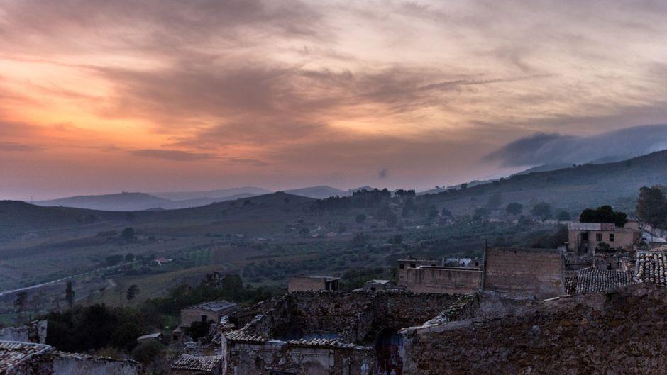 Hinter den wolkenverhangenen Olivenhainen kämpfen sich die Sonnenstrahlen über der Geisterstadt Poggioreale hervor.