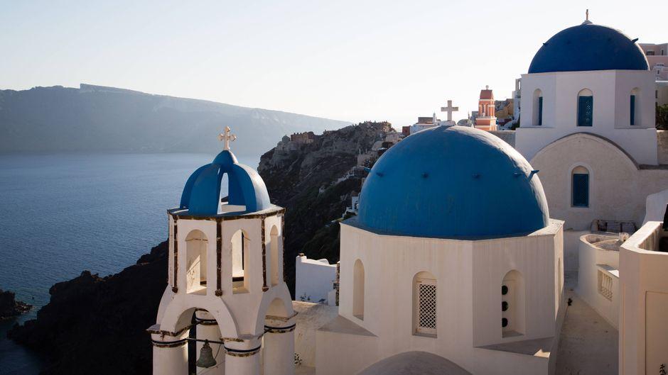 Weiße Kirche mit blauer Kuppel mit Blick aufs Meer auf Santorin.