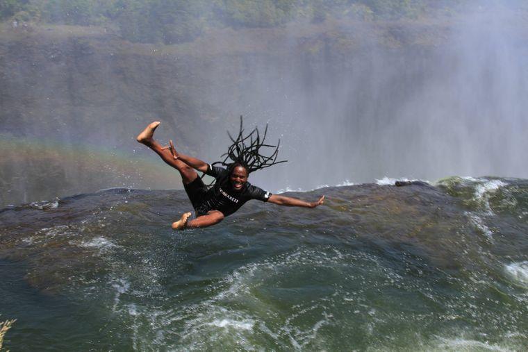 """Ein Mann springt in den """"Devil's Pool"""" an den Victoriafällen an der Grenze zwischen Sambia und Simbabwe."""