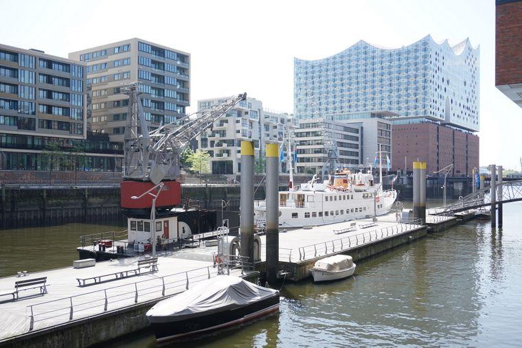 Das Floatel Hafenkran Hamburg im Hamburger Hafen, im Hintergrund die Elbphilharmonie.