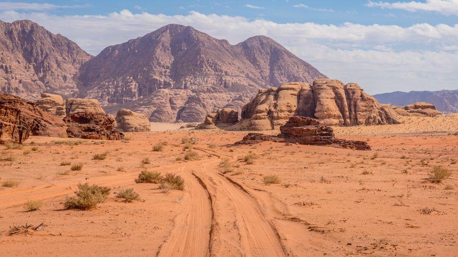 Wüstenstraße und Felsen im Wadi Rum in Jordanien.