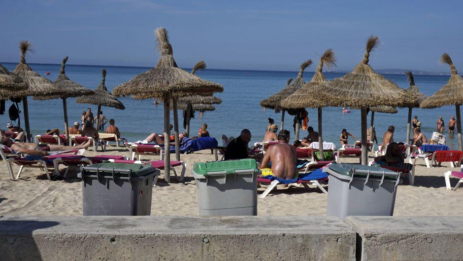 Urlauber liegen beengt am Strand von Mallorca, im Vordergrund Mülltonnen.