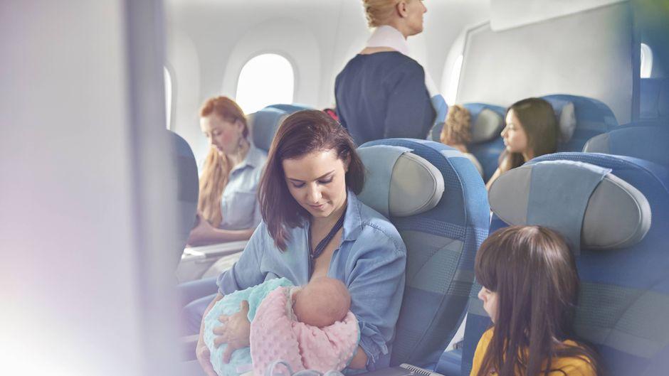 Eine Mutter hält ihr Baby im Flugzeug.