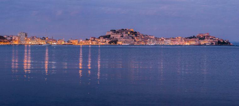 Lichter spiegeln sich zur Abendstunde im Wasser vor Portoferraio, Elba, Toscana, Italien.