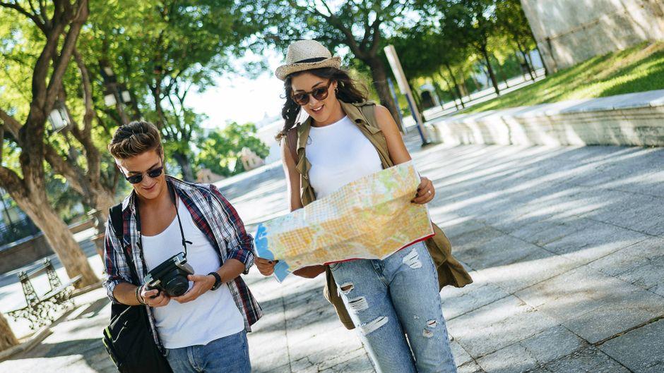 Zwei Touristen mit Kamera und Stadtplan auf einer Städtereise