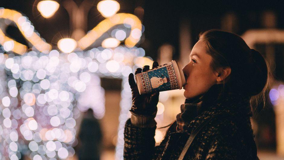 Eine Frau trinkt Glühwein auf einem Weihnachtsmarkt.