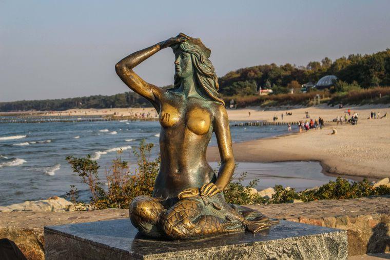 Die Syrenka Ustecka, eine Meerjungfrau aus Bronze mit einem Lachs in der Hand, ist ein Wahrzeichen des Kurortes Ustka in Polen.
