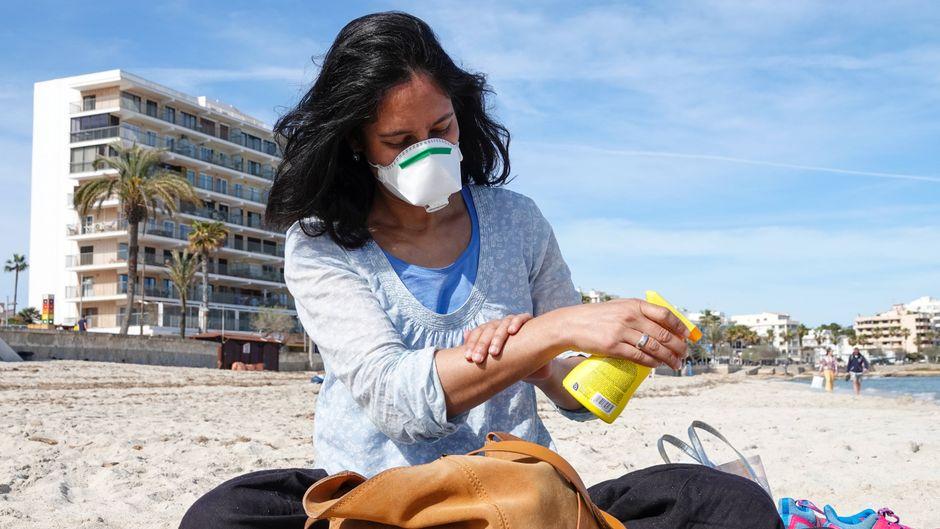 Eine Frau trägt am fast menschenleeren Strand im Urlaubsort Cala Millor einen Mundschutz. (Symbolbild)