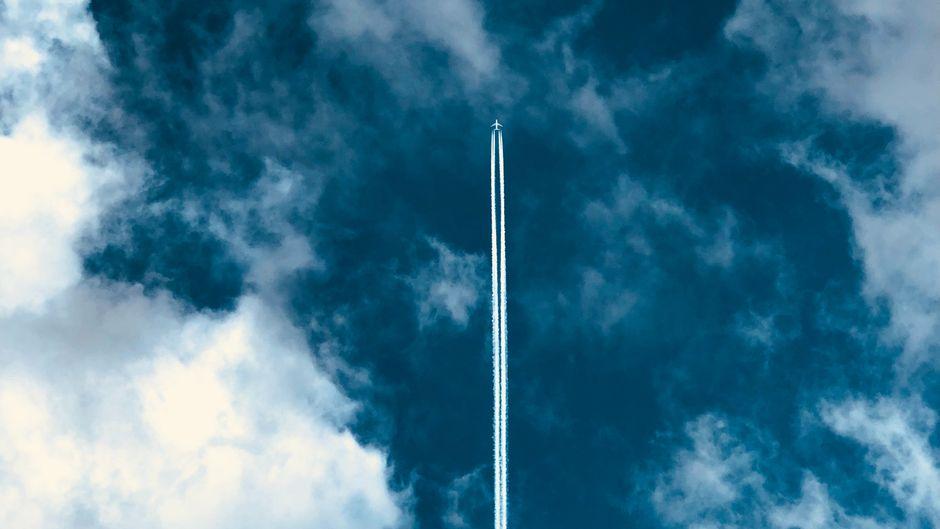 Flugzeug fliegt durch weiße Wolken und hinterlässt einen Kondensstreifen.