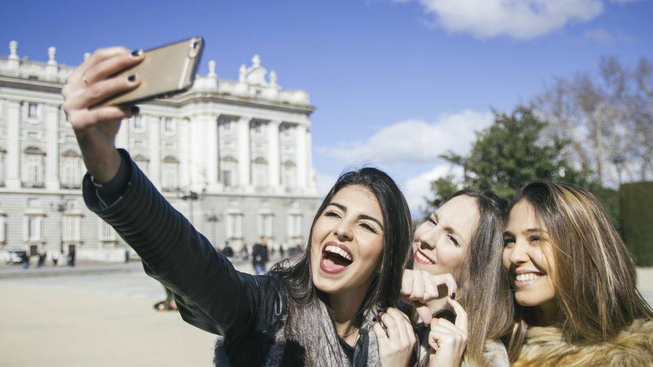 Drei junge Frauen machen in der Sonne ein Selfie in Madrid.