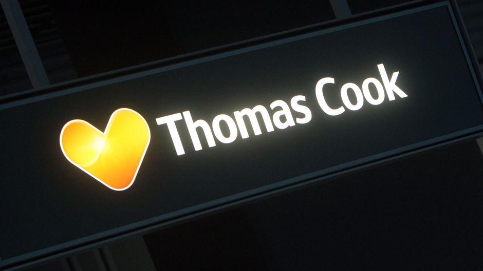 Logo und Schriftzug von Thomas Cook über einem Neckermann-Reisebüro im Flughafen Düsseldorf.