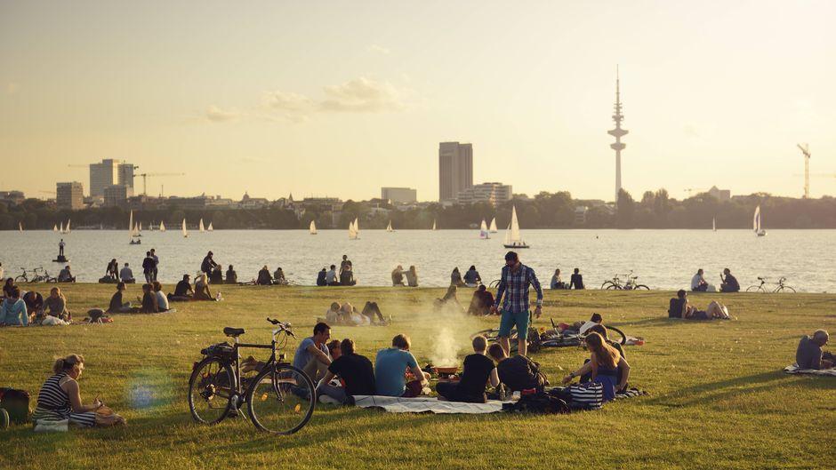 Menschen sitzen in Hamburg an der Außenalster und grillen.
