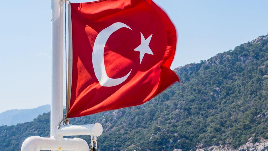 Eine Türkei-Fahne weht vor dem Meer.