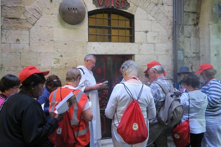 Katholische Pilgerer laufen, begleitet von Priestern, den Kreuzweg.
