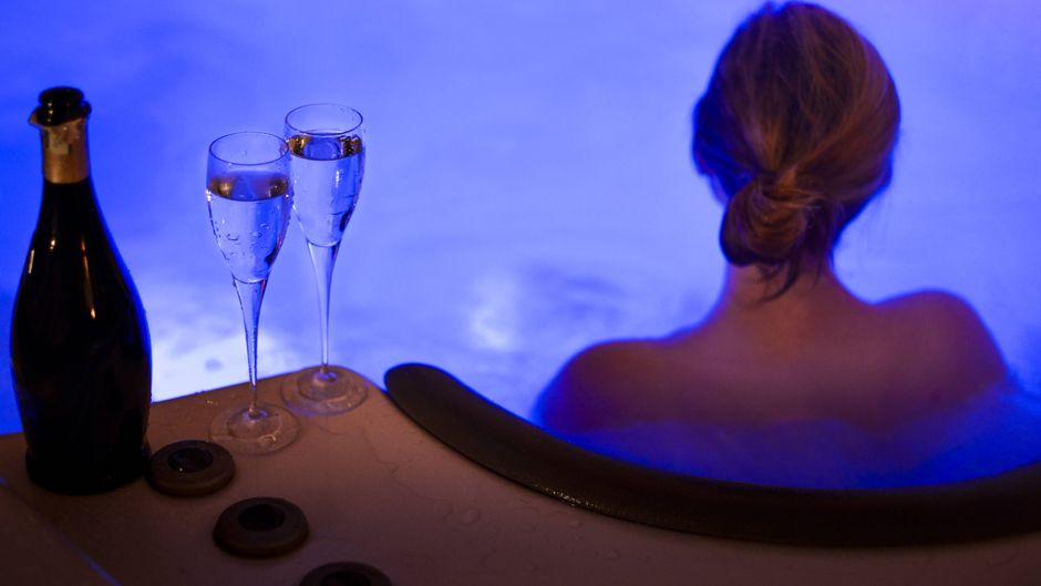 Frau trinkt Champagner im Whirlpool.