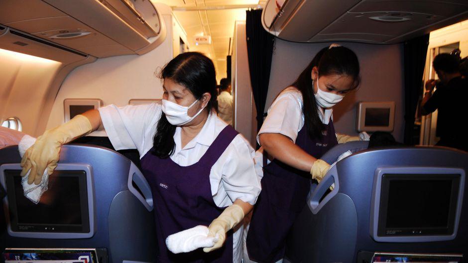 Frauen putzen eine Flugzeugkabine.