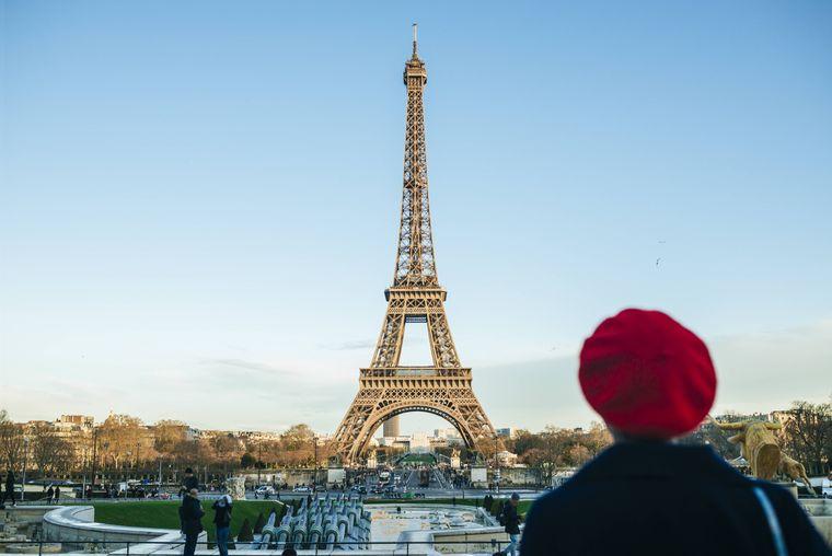 Eine Frau steht mit roter Baskenmütze vor dem Eiffelturm.