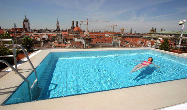 Frau schwimmt im Pool über den Dächern von München  - Dachterrasse des Hotels Oriental Mandarin.