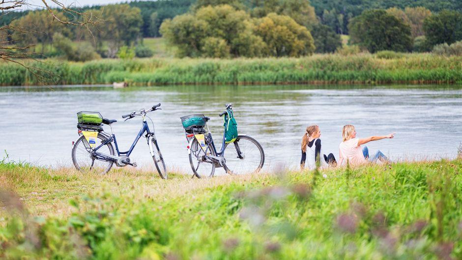 Immer schön langsam: Zwei Fahrradfahrerinnen machen Pause und genießen die Aussicht am Oder-Neiße-Radweg.
