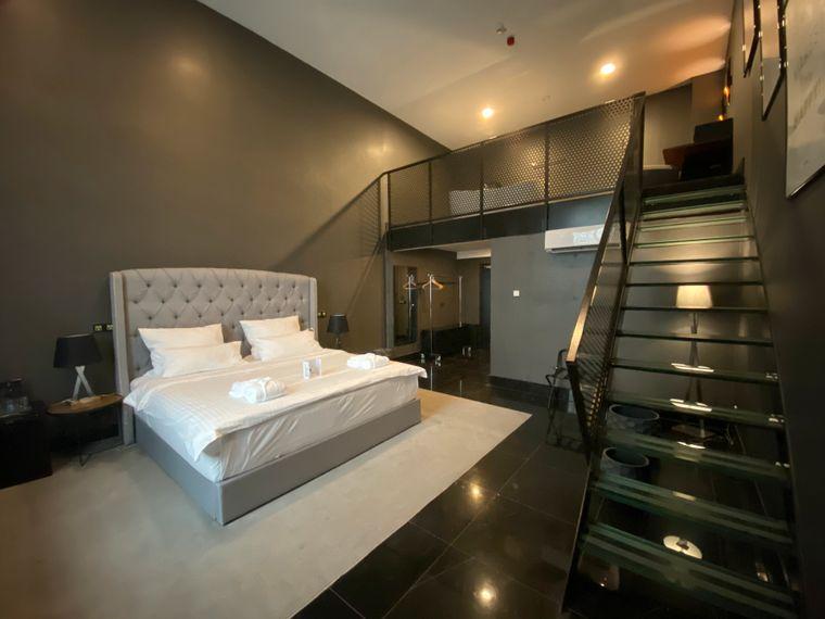 Vom Zimmer mit einem großen Boxspringbett führt eine Glastreppe direkt in eine zweite Etage, wo sich eine freistehende Badewanne befindet.