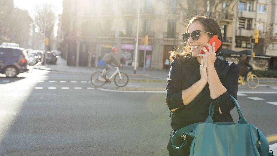 Eine Frau telefoniert auf der Straße – das kostet in der EU bald weniger.