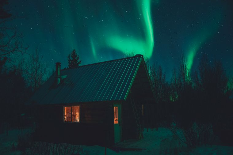 Im dunklen kanadischen Winter erhellen Polarlichter den Himmel über der Hütte.
