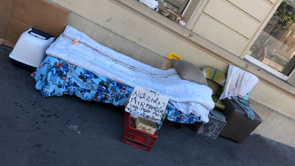 In einer Straße, die zum Arc de Triomphe führt, hat ein Obdachloser sein Quartier aufgeschlagen.