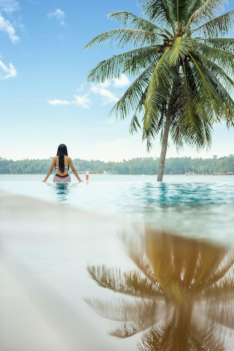 Frau sitzt mit dem Rücken zum Pool unter einer Palme.