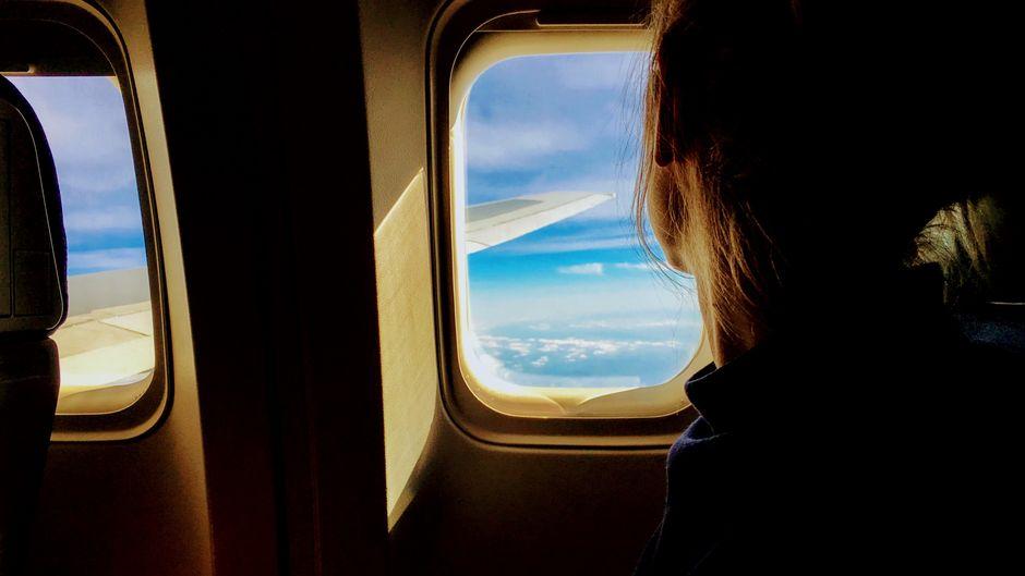 Passagierin schaut aus dem Fenster im Flugzeug.