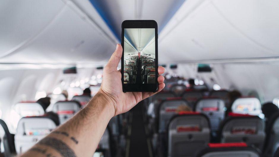 Mann fotografiert leeres Flugzeug mit dem Smartphone.