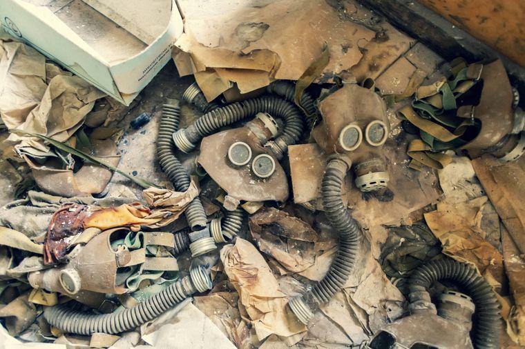 Verstaubte Gasmasken liegen auf dem Boden verteilt.