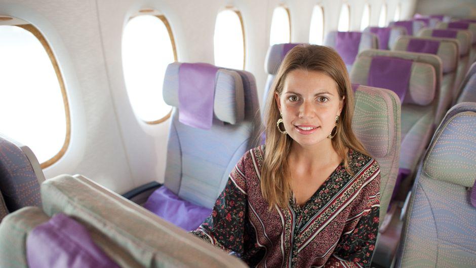 Eine Passagierin auf dem Mittelsitz im Flieger.