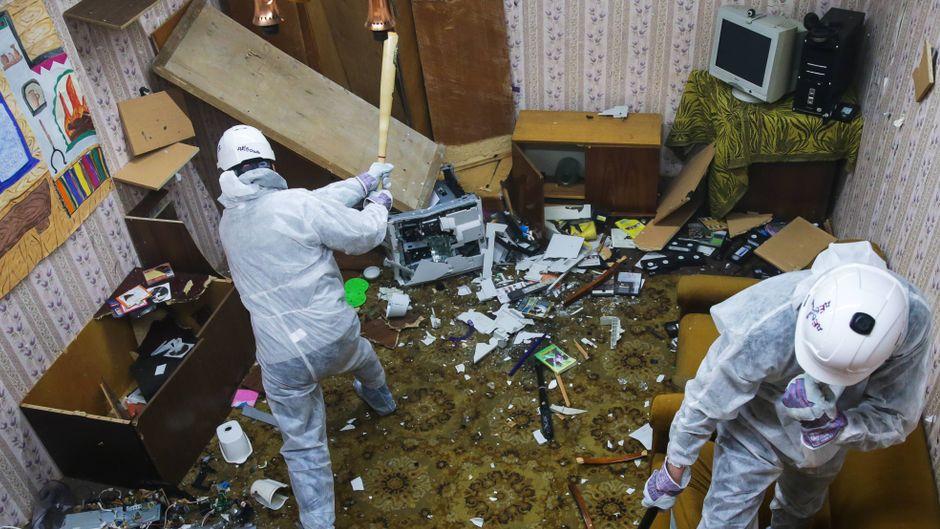 Zwei Männer schlagen in einem Rage Room in Russland alles klein.