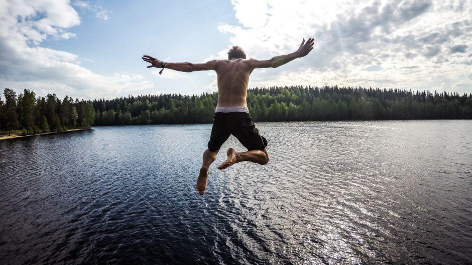Ein Mann in Badehose springt in einen See in Finnland.