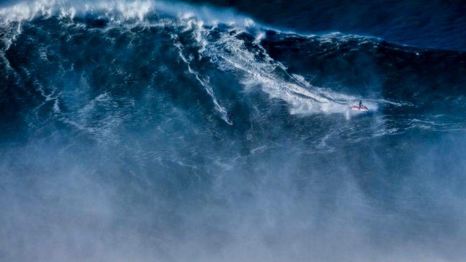 Der Brasilianer Rodrigo Koxa ist auf seiner Weltrekordwelle in Portugal kaum zu erkennen.