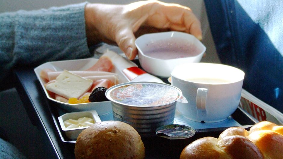 Passagier isst ein Frühstück an Bord eines Flugzeuges