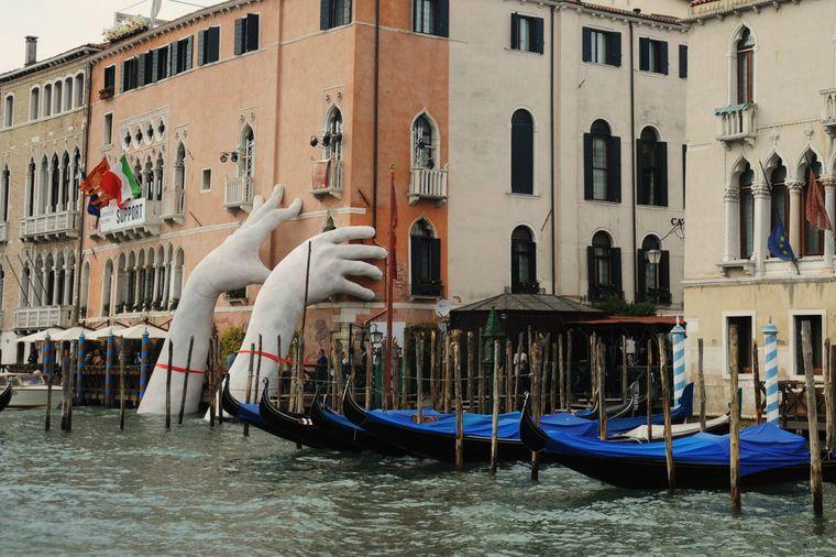 Zwei Hände stützen symbolisch ein historisches Gebäude in Venedig.