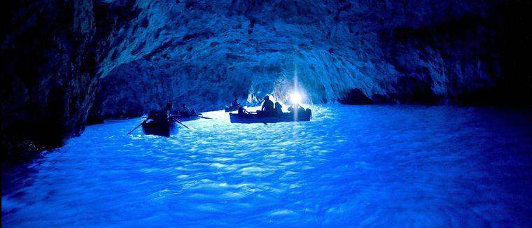 Boote in der Blauen Grotte auf Capri in Italien.