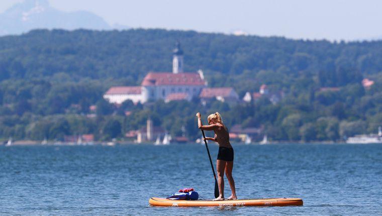Wassersportler am Ammersee. Hier eine Stand-Up-Paddlerin mit dem Marienmünster Dießen im Hintergrund.