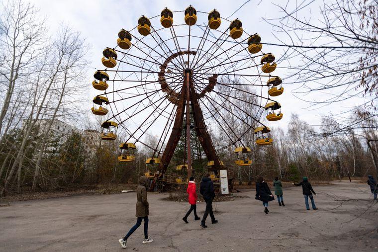 Touristen laufen durch den verlassenen Freizeitpark in Prypjat.